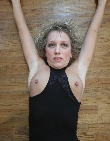 Older blonde flashes her tits and twat in all black ensemble on hardwood floor