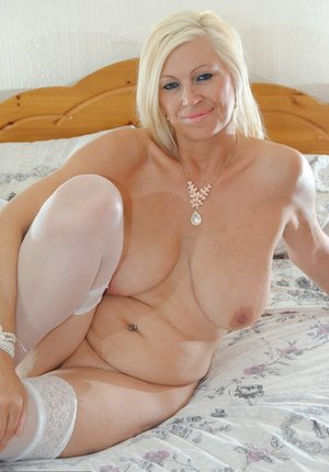 Mature model Platinum Blonde fondles her saggy tits and twat while on her bed